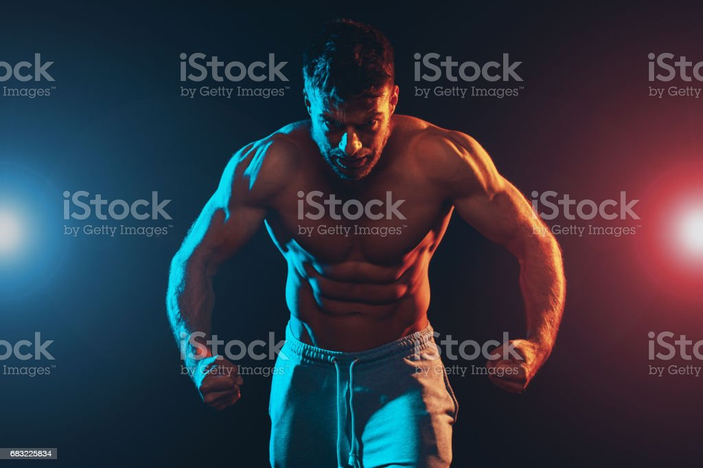 Shirtless handsome muscle man posing in the studio stock photo
