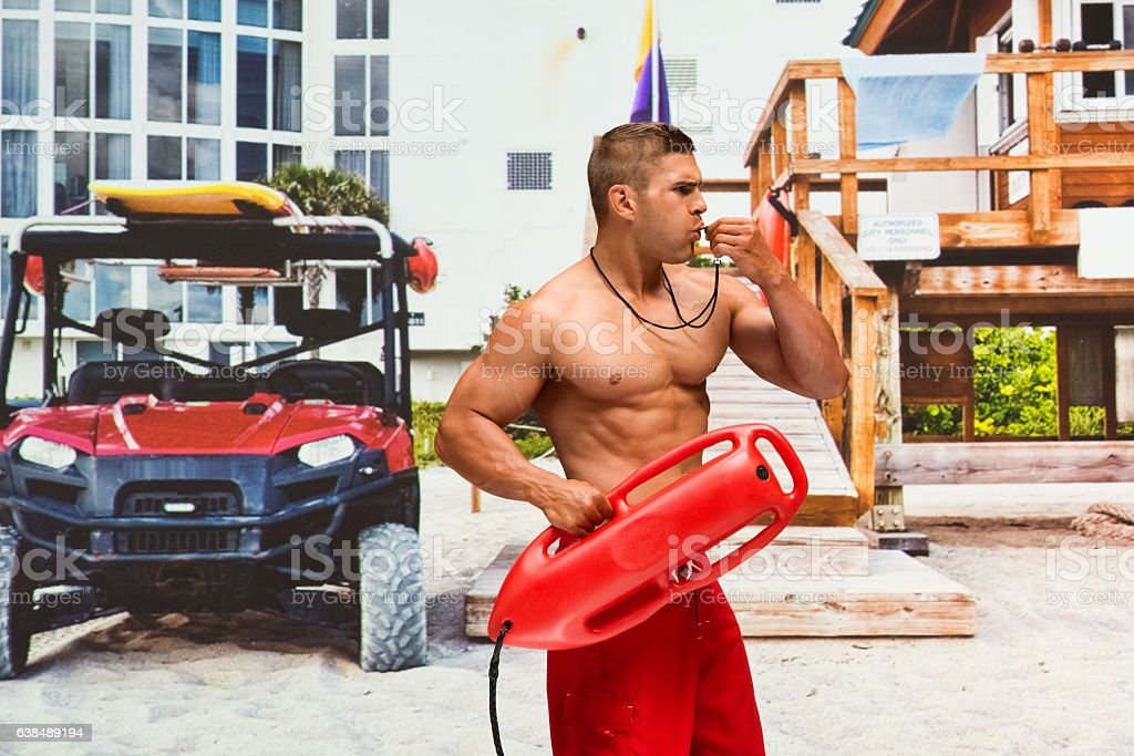 Shirtless lifeguard whistling outdoors stock photo