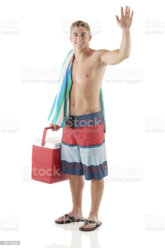 Shirtless man carrying a cooler and waving hand royalty-free stock photo