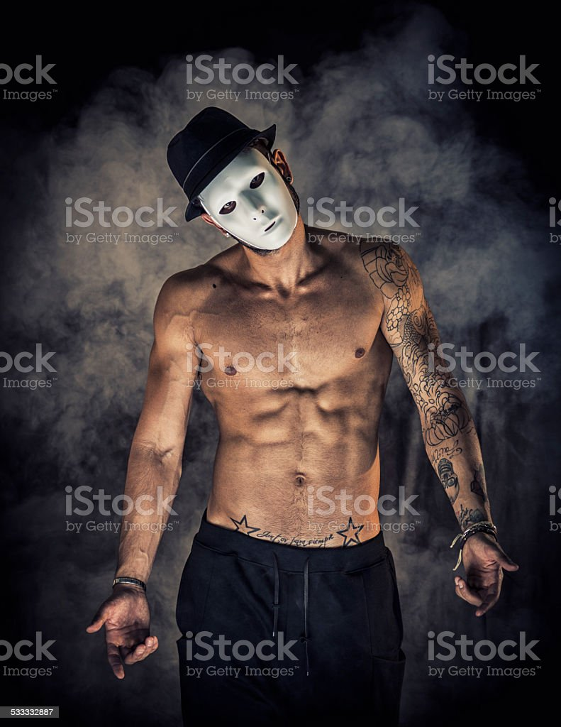 Shirtless man dancer or actor with creepy, scary mask stock photo