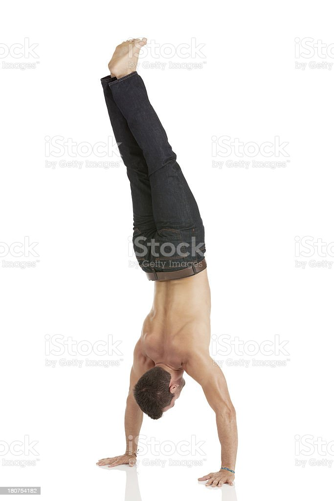 Shirtless man doing handstand royalty-free stock photo