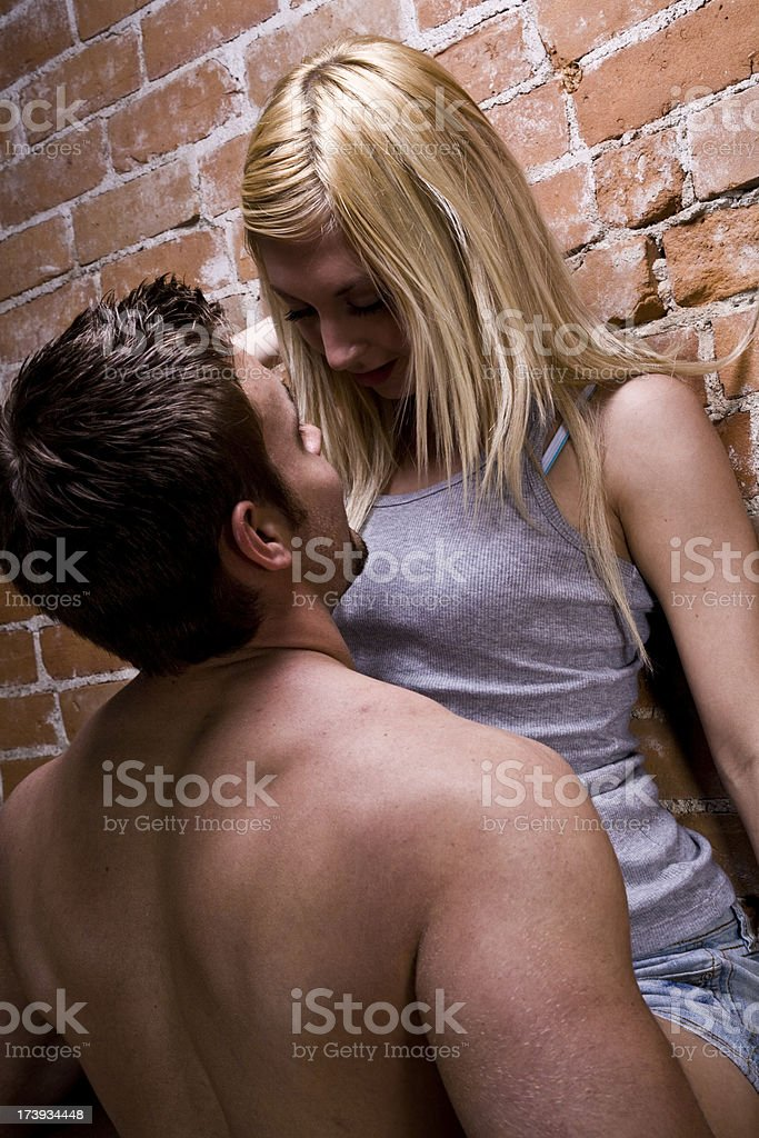 Shirtless man hoisting blonde woman up against brick wall royalty-free stock photo