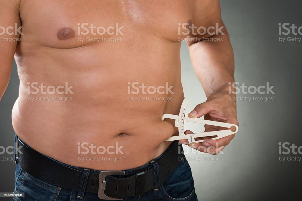 Shirtless Man Measuring Stomach Fat With Caliper stock photo