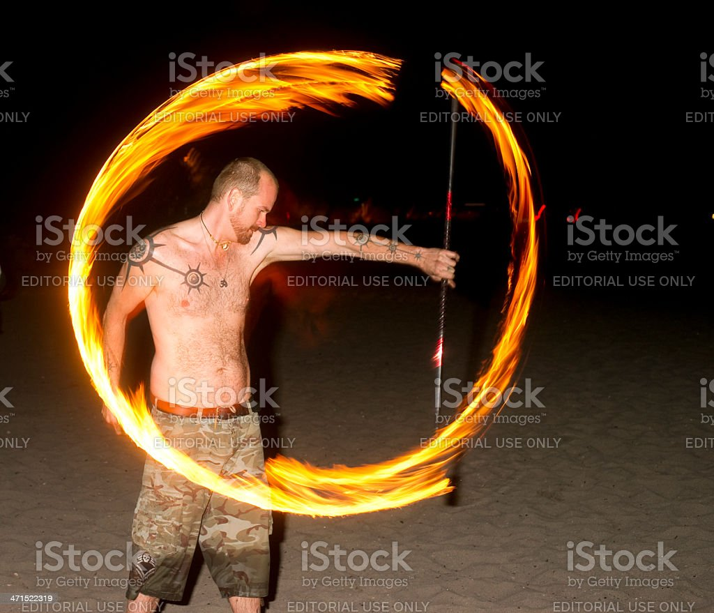 Shirtless Man on Beach Spins Burning Rod Playing with Fire stock photo