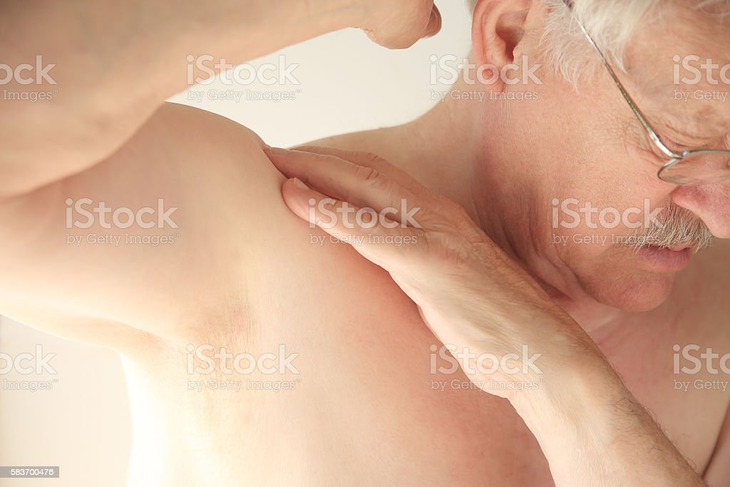 Shirtless man with aching shoulder stock photo