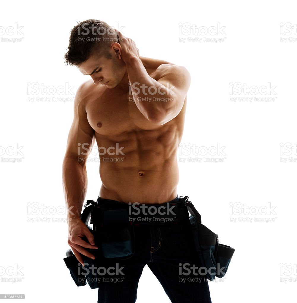 Shirtless muscular building contractor looking down stock photo