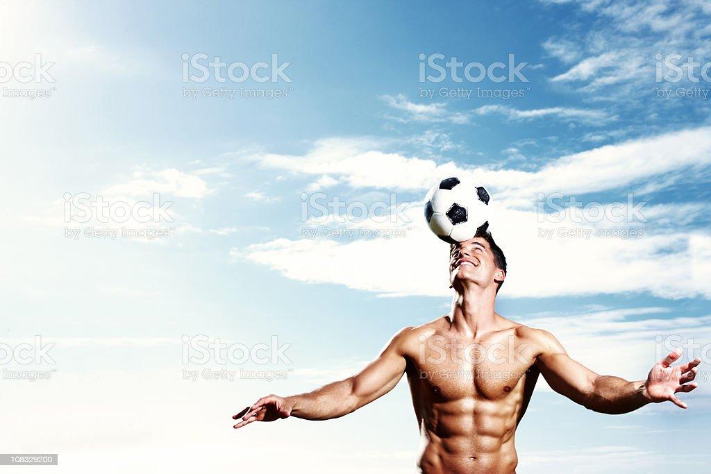 Shirtless muscular guy balancing football on head royalty-free stock photo