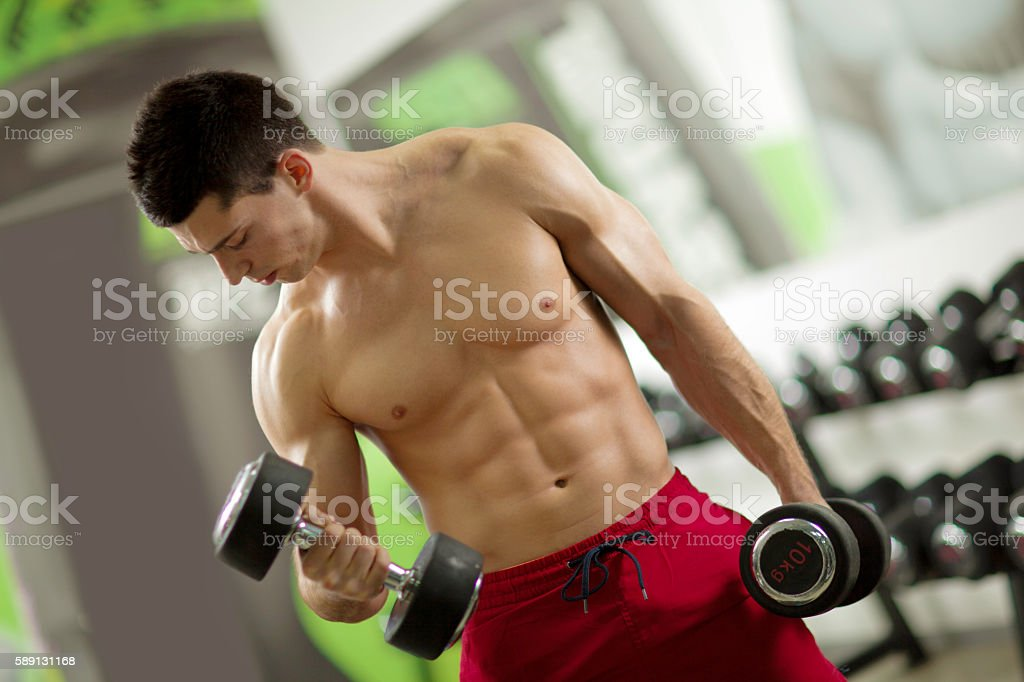 Shirtless muscular man doing dumbbell exercises  at the gym. stock photo
