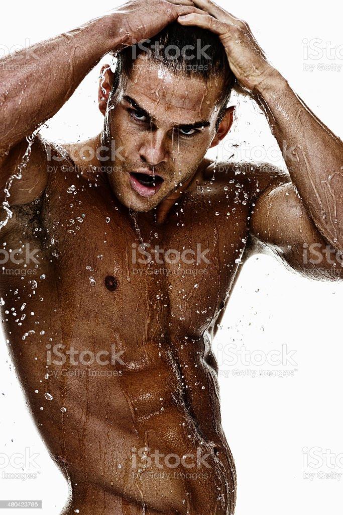 Shirtless muscular man having shower stock photo