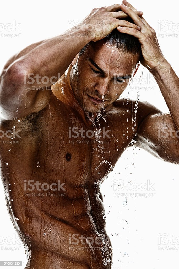 Shirtless muscular man having shower stock photo