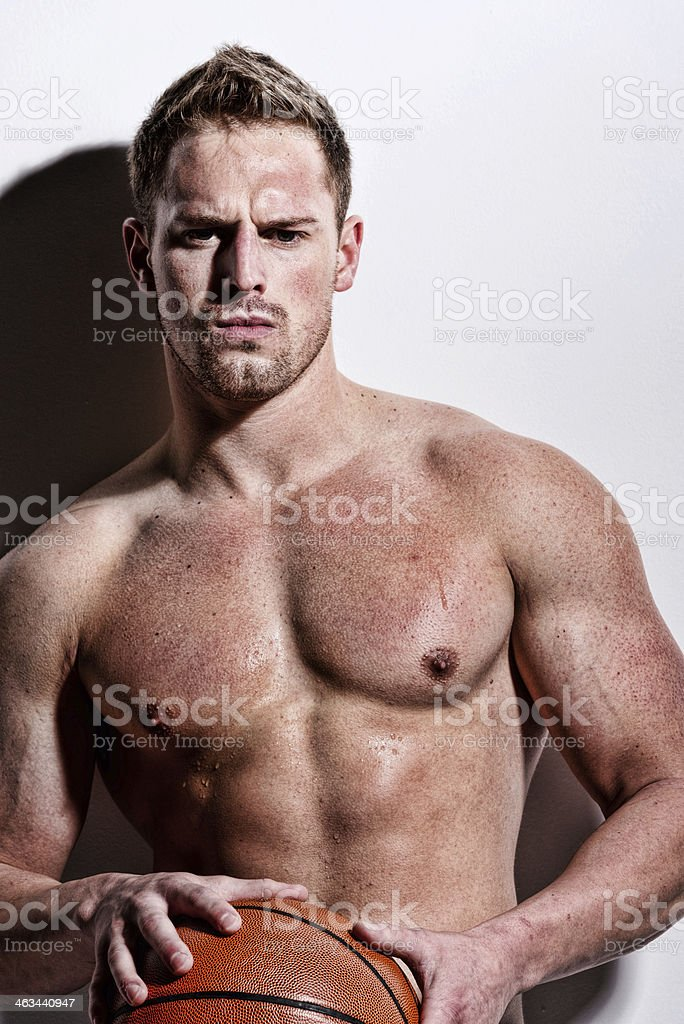 Shirtless muscular man holding a basketball royalty-free stock photo