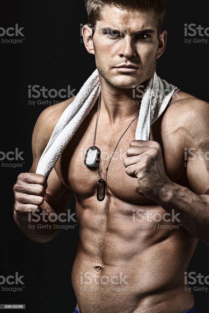 Shirtless muscular man holding towel stock photo