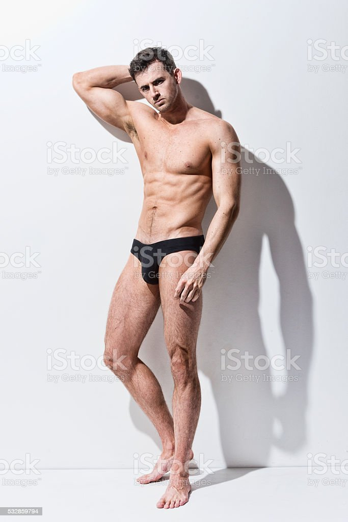 Shirtless muscular man leaning against wall stock photo