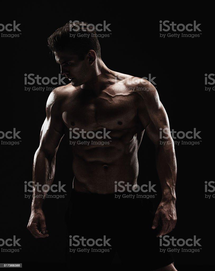 Shirtless muscular man looking away stock photo