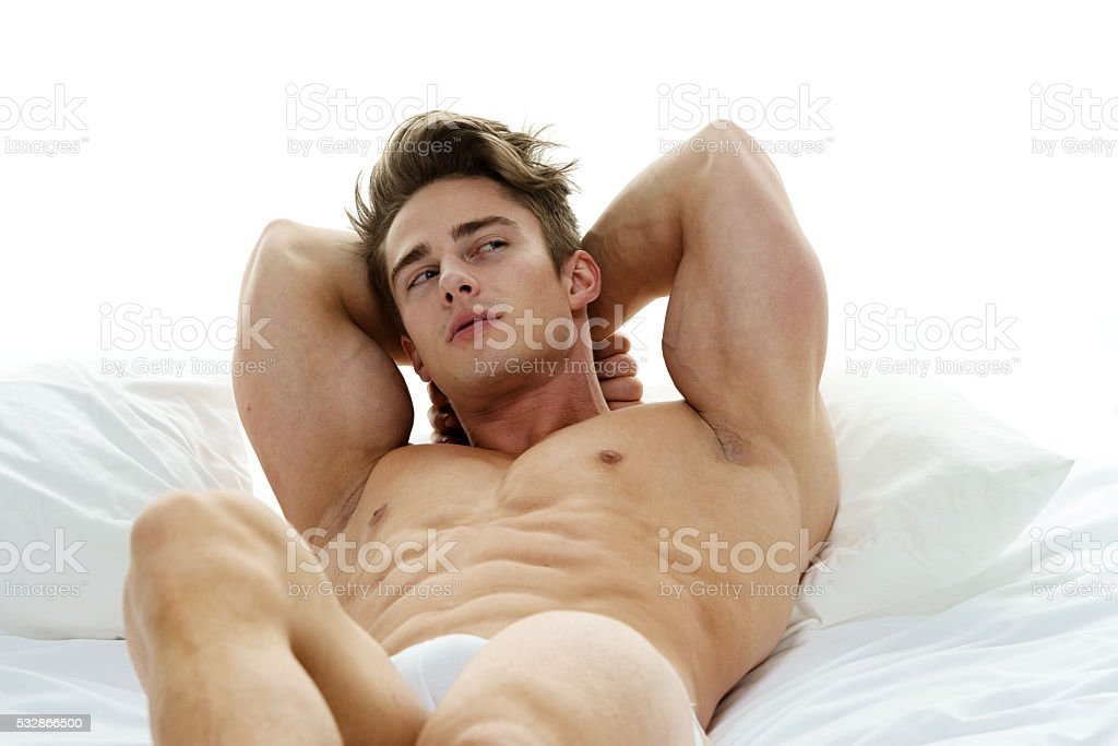 Shirtless muscular man lying on bed stock photo