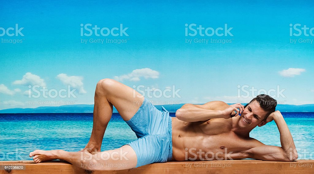 Shirtless muscular man on phone outdoors stock photo