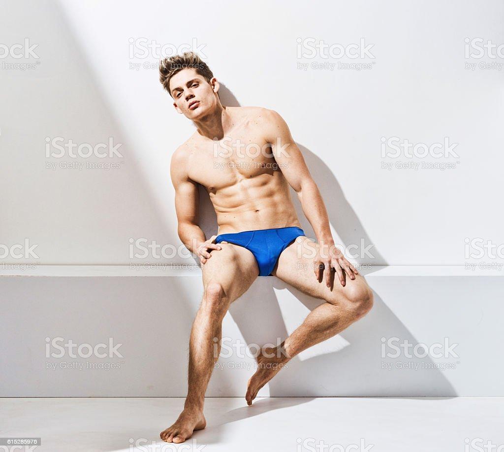 Shirtless muscular man sitting on box stock photo