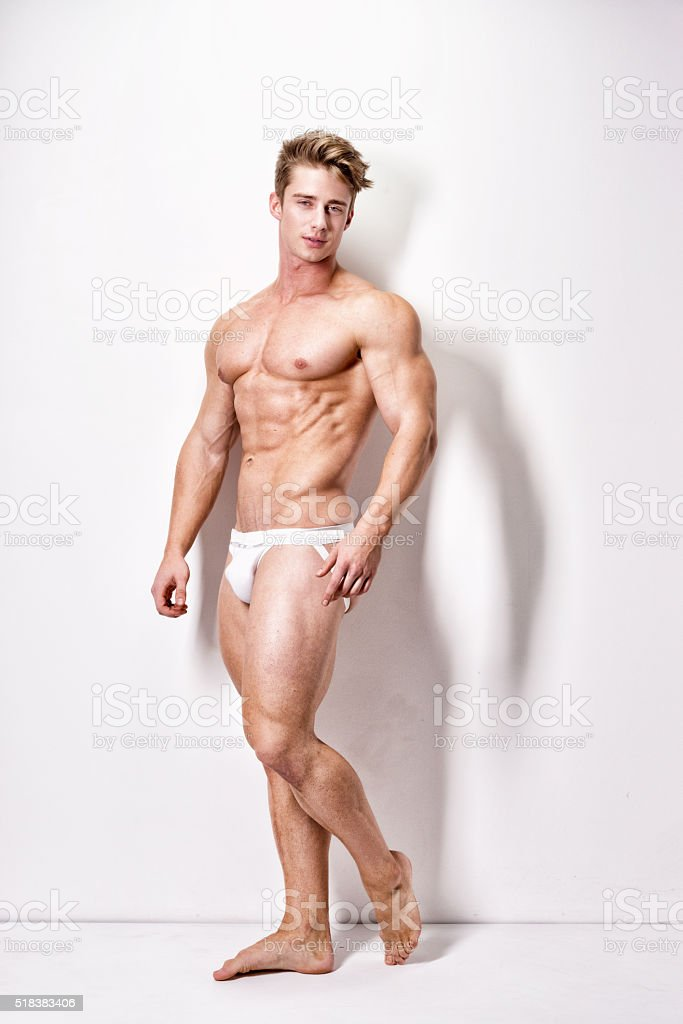 Shirtless muscular man standing and looking away stock photo