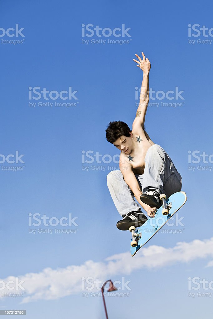A shirtless skateboarder jumping up high in the air royalty-free stock photo