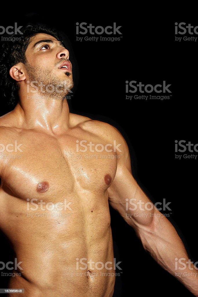 A shirtless, sweaty man exercising in black background. royalty-free stock photo