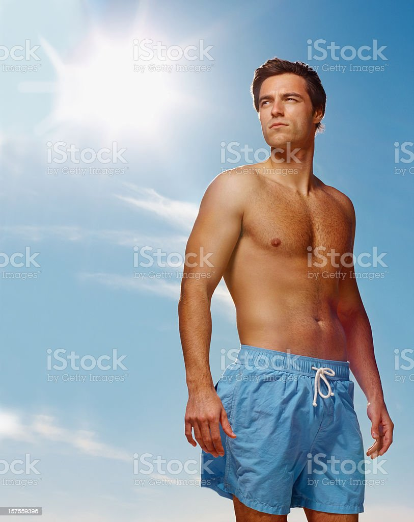 Shirtless young guy standing alone  against the blue sky royalty-free stock photo