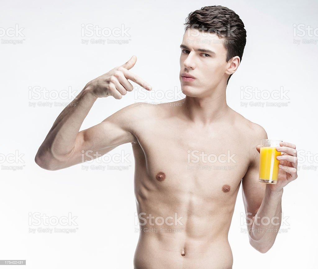 shirtless young man holding glass of orange juice stock photo