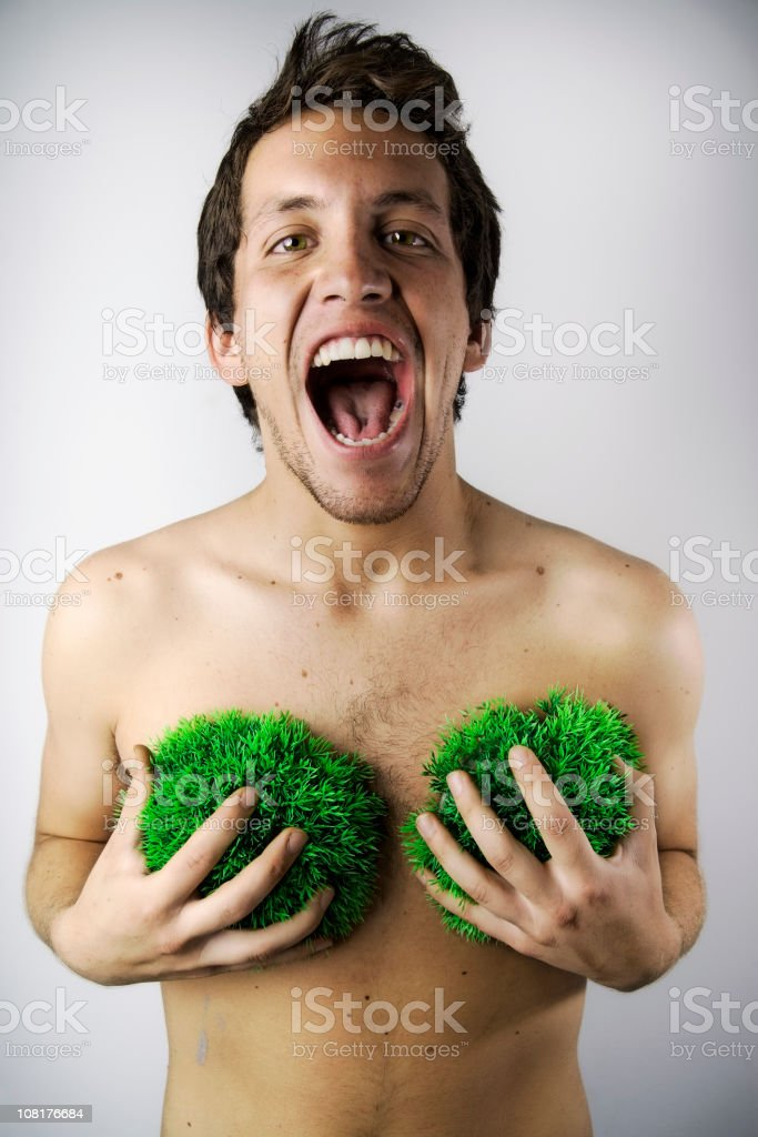 Shirtless Young Man Holding Tufts of Grass Against His Chest royalty-free stock photo