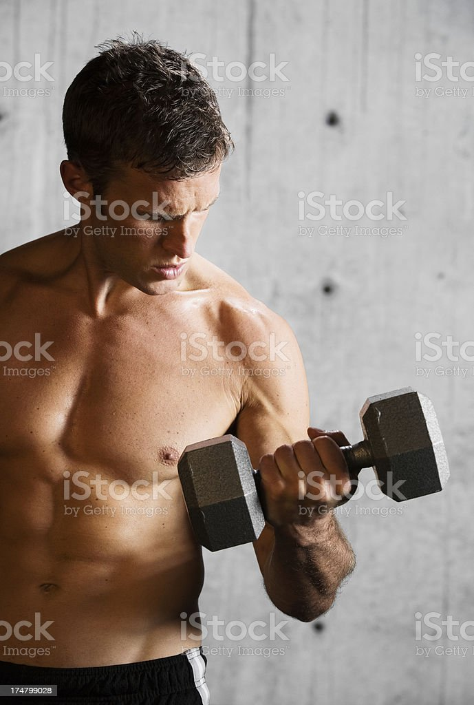 Shirtless young man lifting dumbbell. royalty-free stock photo