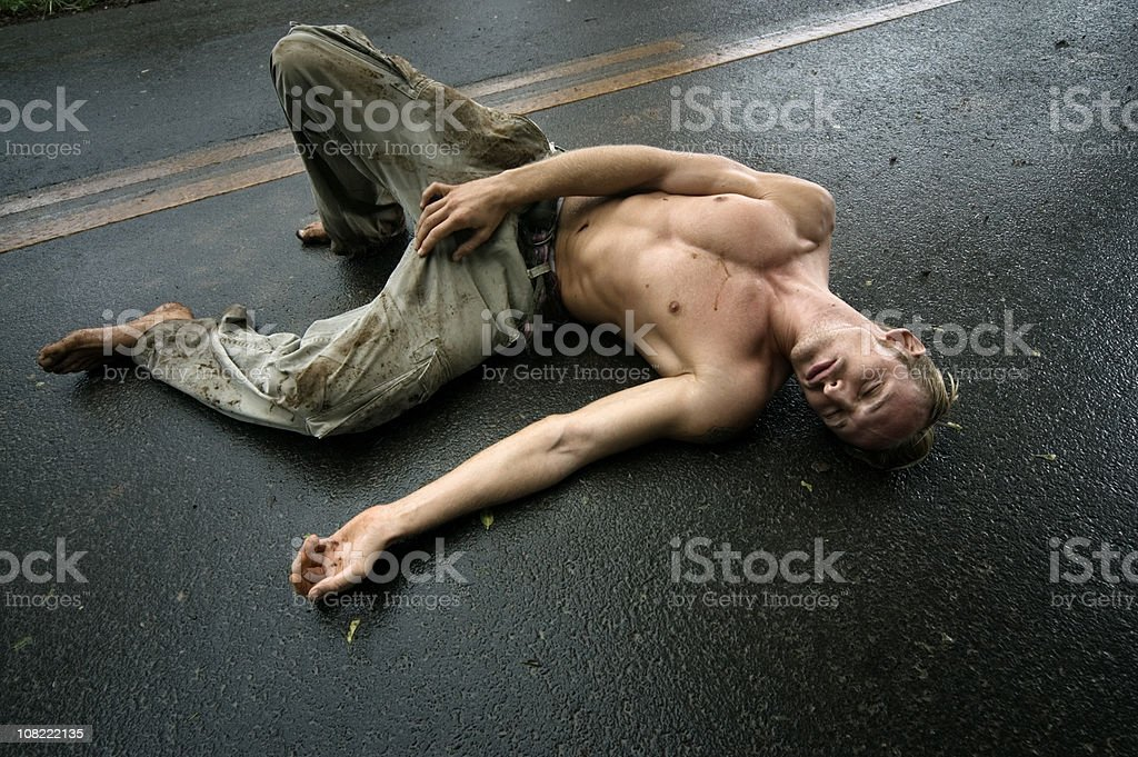 Shirtless Young Man Lying in Middle of Wet Road royalty-free stock photo