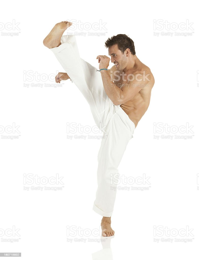 Shirtless young man practicing capoeira royalty-free stock photo