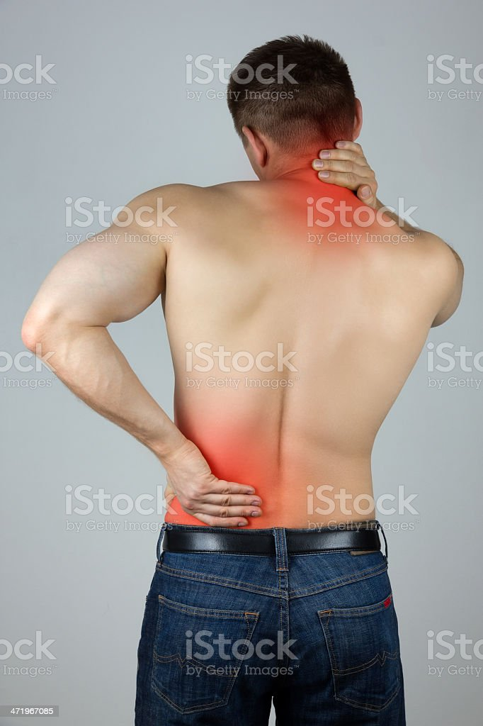 Shirtless young man rubbing lower back and neck in pain stock photo