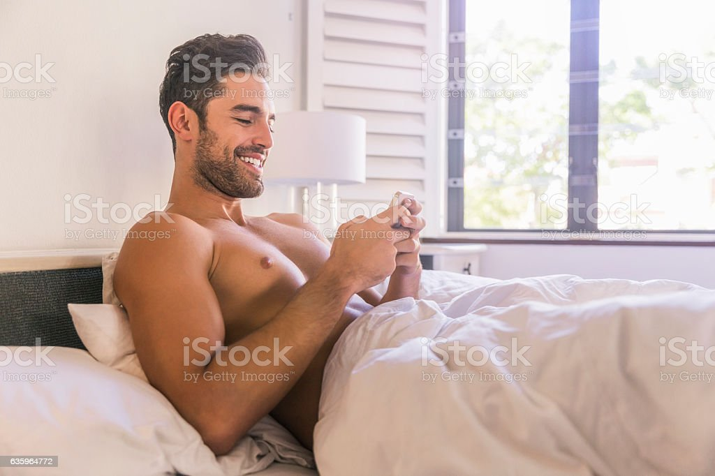 Shirtless young man using smart phone in bed stock photo
