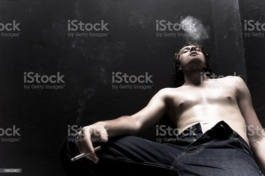 Shirtless Young Man with Unbuttoned Jeans Blowing Cigarette Smoke royalty-free stock photo