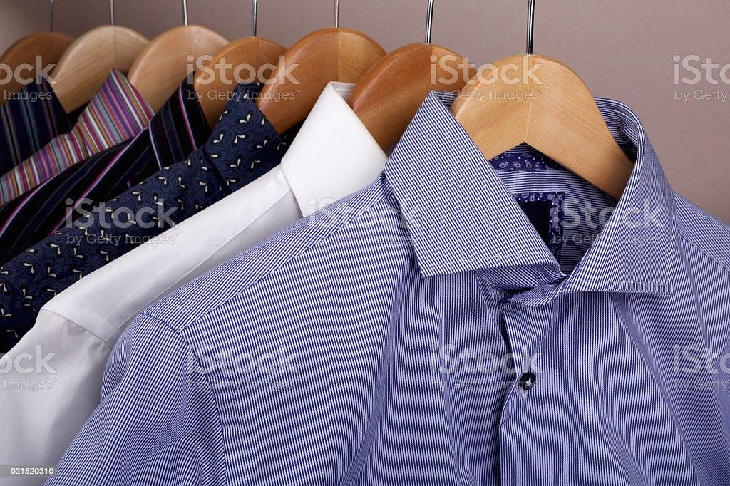 Shirts hanging on wooden coat hangers stock photo