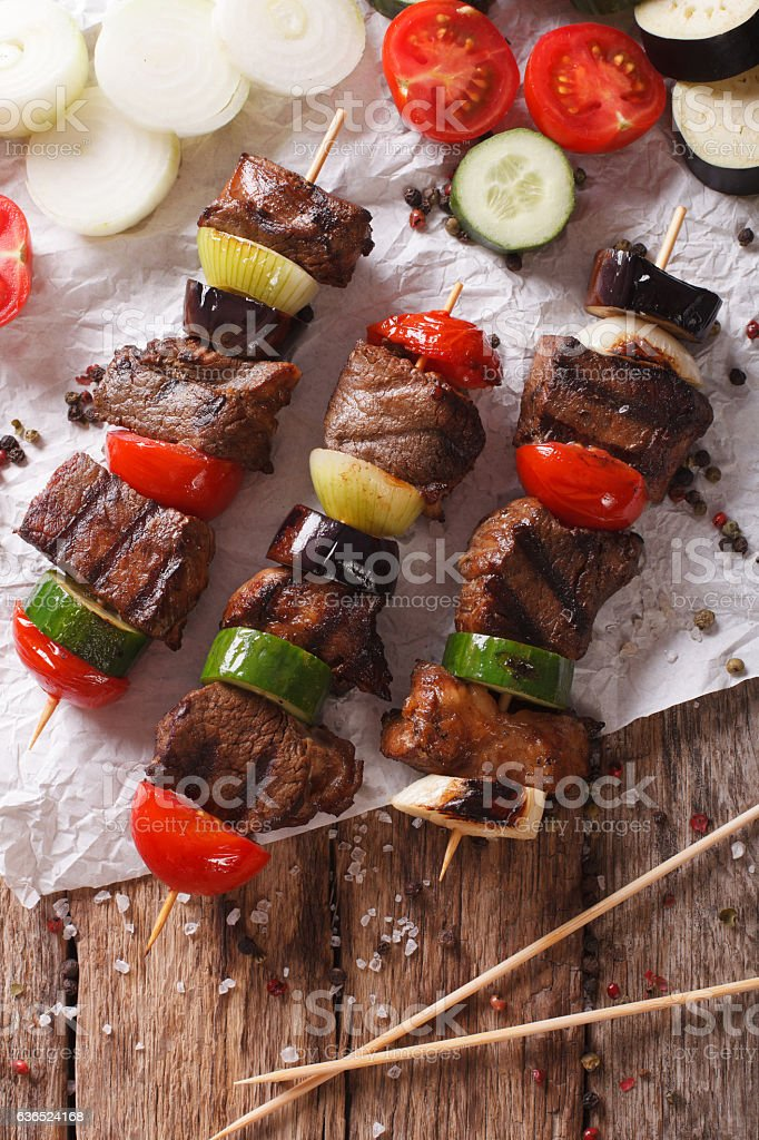 Shish kebab on skewers with vegetables close-up. vertical top view stock photo