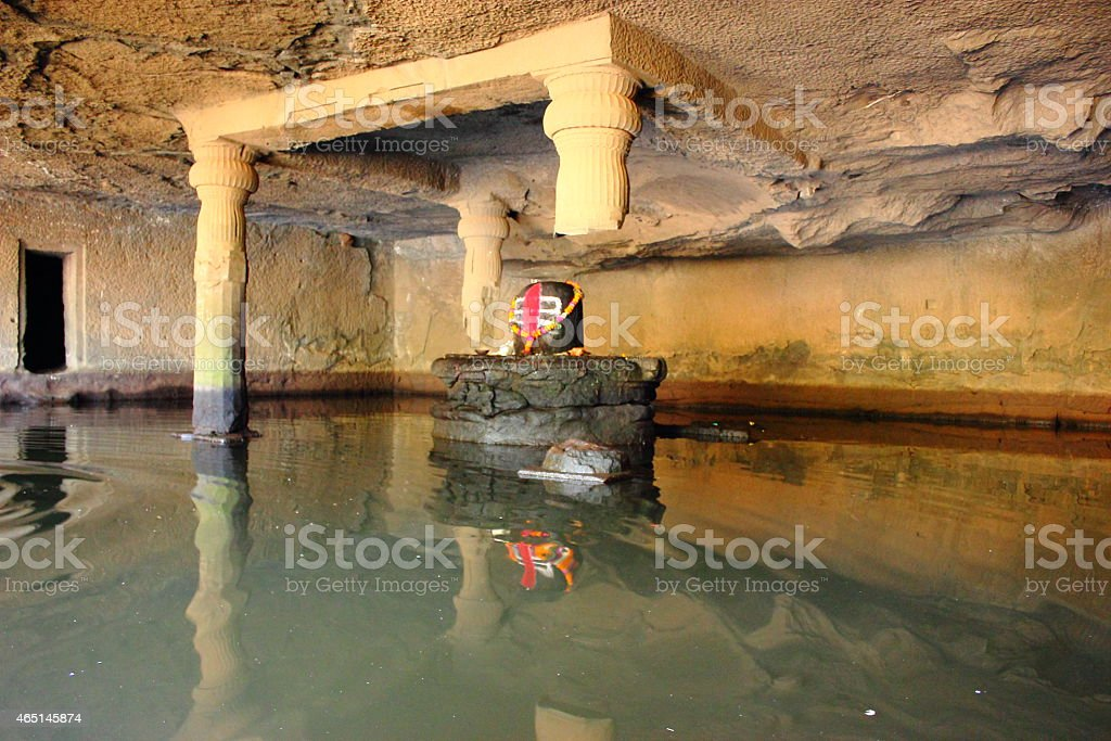 Shivalinga in a cave surrounded by water stock photo