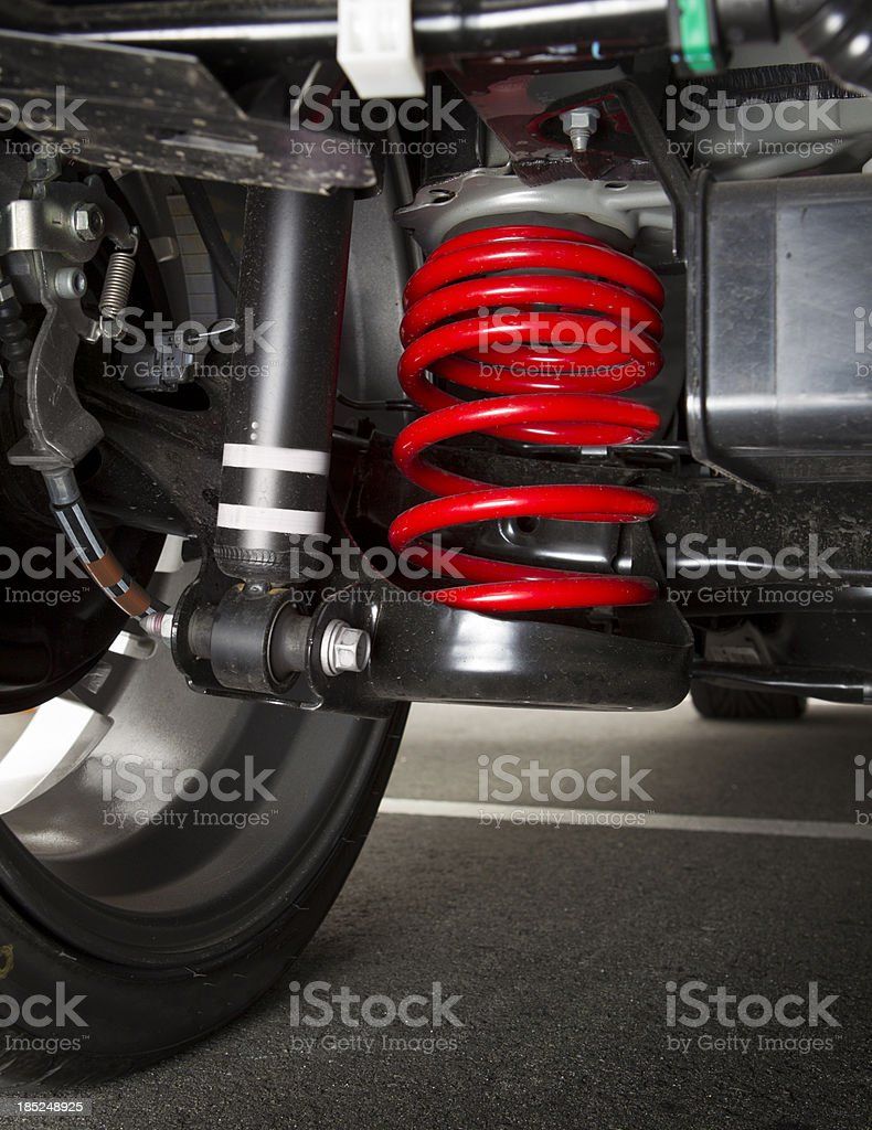 Shock spring under a car tire stock photo