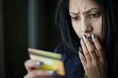 Shocked and worried young woman looking at credit card.
