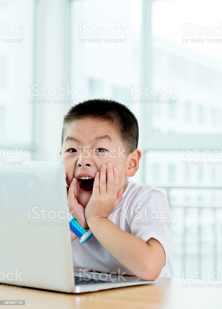 Shocked asian boy on the internet with laptop computer stock photo