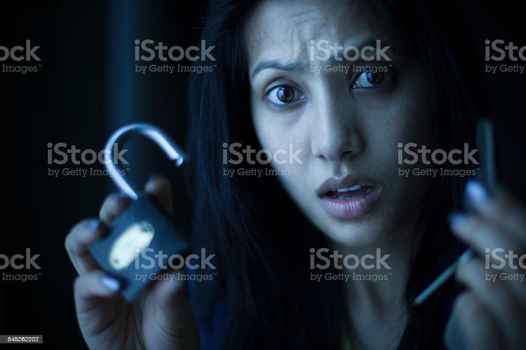 Shocked Asian young woman showing padlock and key at camera. stock photo