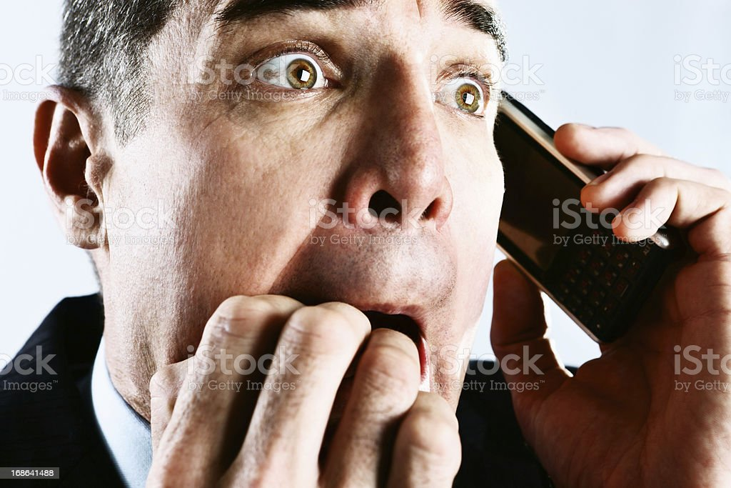 Shocked businessman biting nails in panic at phone call royalty-free stock photo