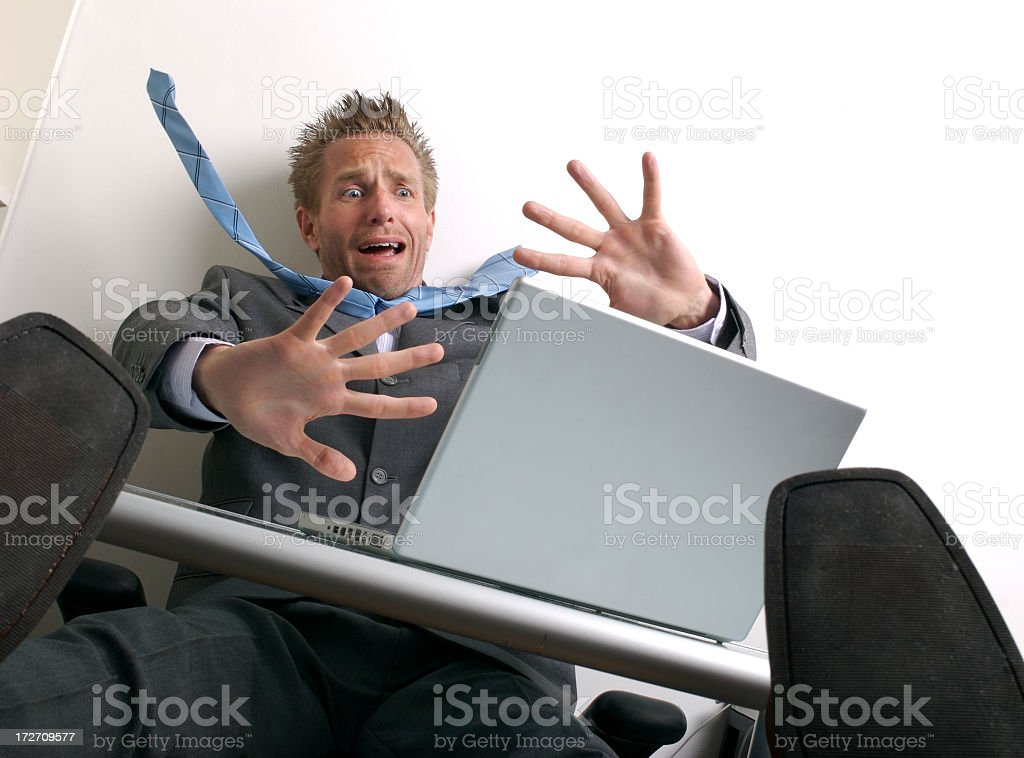 Shocked Businessman Freaking Out at Topsy-Turvy Desk Laptop royalty-free stock photo