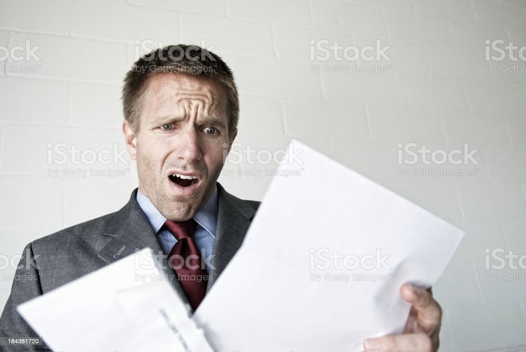Shocked Businessman Looks Disappointed Opening a Letter stock photo