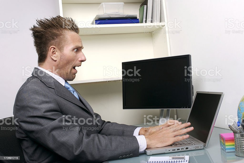 Shocked Businessman Office Worker Sitting at Office Cubicle stock photo