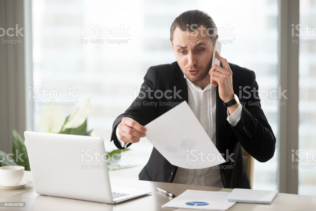 Shocked businessman talks on the phone holding financial report document. stock photo