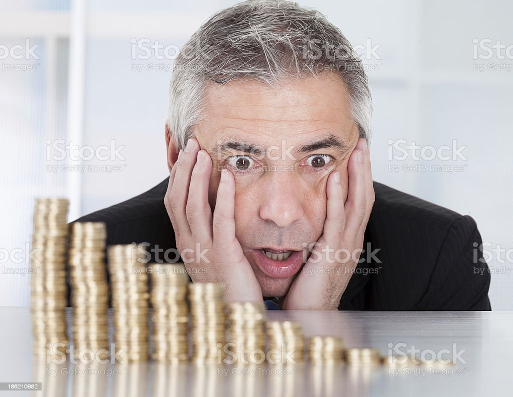 Shocked Businessman With Stack Of Coins stock photo