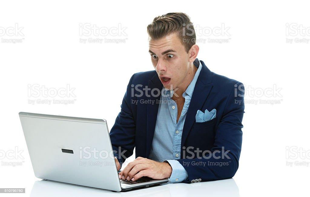 Shocked businessman working on laptop stock photo