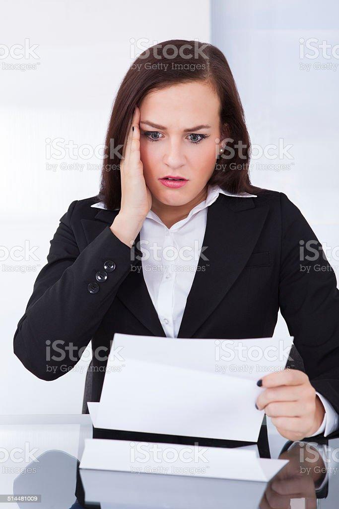 Shocked Businesswoman Reading Document stock photo