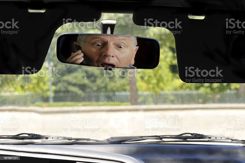 Shocked driver on cellphone in rear view mirror stock photo