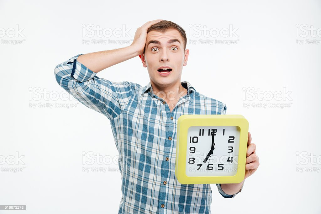Shocked excited young man holding big clock stock photo